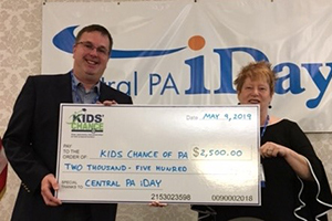 KCPA Board Member Michael Lehr is receiving a check from Angela Tennis, Central PA iDay Board Member